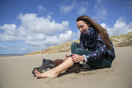 Young woman taking her hiking boots off on the beach at Harlech.の写真素材 [FYI02858120]