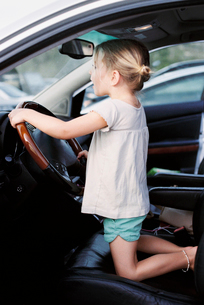 Young girl kneeling on the drivers seat of a car, holding the steering wheel, 有etending to drive.の写真素材 [FYI02858126]