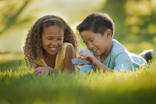 Two children lying on the grass, one holding a small terrapin or turtle.の写真素材 [FYI02858131]