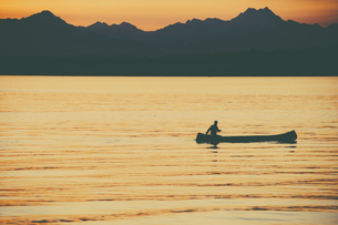 A person seated in a large Indian style canoe paddling across calm water at sunset.の写真素材 [FYI02858133]