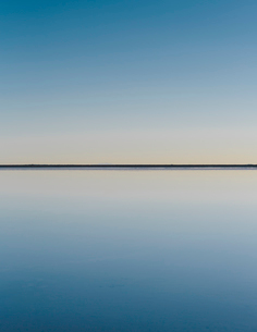 The view to the clear line of the horizon where land meets sky, across the flooded surface of Bonnevの写真素材 [FYI02858134]
