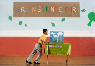 A boy pushing a table into a room at the Green Science Fair.の写真素材 [FYI02858138]