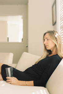 Woman with long blond hair wearing a black dress, sitting on a sofa, holding a glass.の写真素材 [FYI02858139]