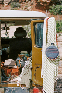 Outdoor gear including clothing, a hat, boots, bag, camera and a water bottle in the back of a 4x4.の写真素材 [FYI02858144]