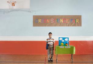 A boy standing under a Green Science Fair sign beside a Solar Power presentation.の写真素材 [FYI02858151]