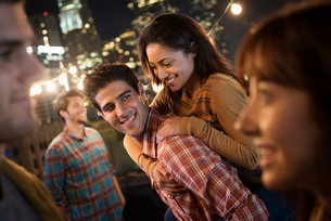 A group of men and women at a rooftop party with a view over the city.の写真素材 [FYI02858154]