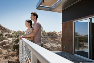 A man and woman on the terrace of an eco home, a low impact house in the desert landscape.の写真素材 [FYI02858156]