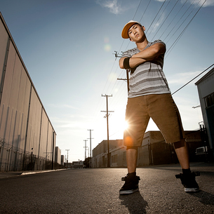 A young man, a breakdancer standing on a street with arms folded.の写真素材 [FYI02858157]