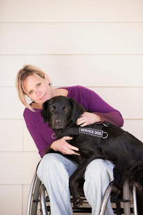 A mature woman wheelchair user with her arms around her service dog, a black Labrador whose front paの写真素材 [FYI02858164]