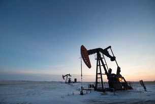 An oil drilling rig and pumpjack on a flat plain in the Canadian oil fields at sunset.の写真素材 [FYI02858165]