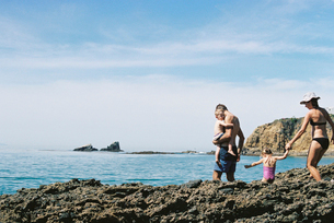 A family on holiday, two adults with their son and daughter walking across rocks by the ocean.の写真素材 [FYI02858169]