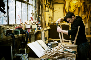 A man working in a furniture maker's workshop. Windsor chairs.の写真素材 [FYI02858178]