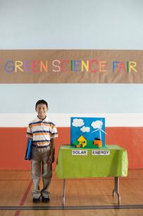 A boy standing under a Green Science Fair sign beside a Solar Power presentation.の写真素材 [FYI02858183]