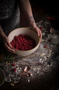 Valentine's Day baking, woman preparing fresh raspberries in a bowl.の写真素材 [FYI02858186]
