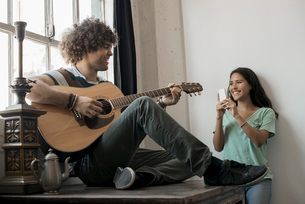 Loft living. A young man playing guitar to an appreciative audience, a young woman holding a smart pの写真素材 [FYI02858187]