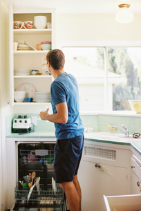 Rear view of a man standing in front of a cupboard with crockery in a kitchen.の写真素材 [FYI02858189]