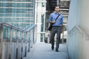 A man carrying a computer bag with a strap across his chest on along a city walkway.の写真素材 [FYI02858194]
