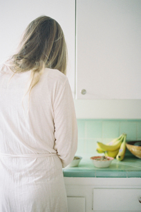Rear view of a woman standing in a kitchen, 有eparing breakfast.の写真素材 [FYI02858207]