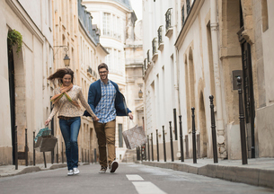 A couple walking along a narrow street in a historic city centre, with shopping bags.の写真素材 [FYI02858213]