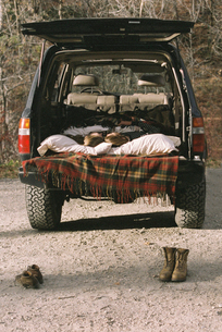 Young couple sleeping in the back of their car, boots standing on the ground in foreground.の写真素材 [FYI02858222]