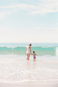 Woman standing hand in hand with her daughter on a sandy beach watching a wave.の写真素材 [FYI02858228]