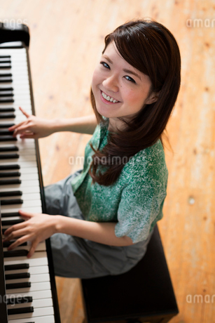 Young woman playing on a grand piano in a rehearsal studio.の写真素材 [FYI02858230]