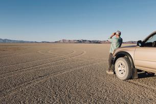 Man standing on vast desert, looking through binoculars and leaning against truck, Black Rock Desertの写真素材 [FYI02858242]