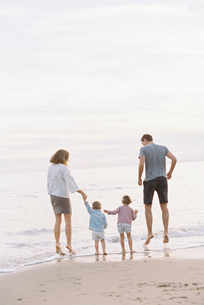 Couple playing with their son and daughter on a sandy beach by the ocean, holding hands.の写真素材 [FYI02858262]