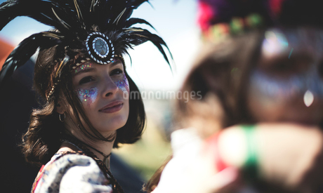 Young woman at a summer music festival face painted, wearing feather headdress, looking at camera.の写真素材 [FYI02858270]