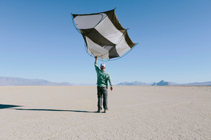 Man holding a capsule pod camping tent above his head in the open space of the desert.の写真素材 [FYI02858271]