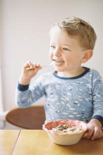 Young boy sitting at a table, eating breakfast from a bowl.の写真素材 [FYI02858278]