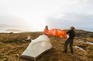 Two men holding and putting up a small tent in open space. Wild camping.の写真素材 [FYI02858281]