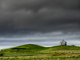 A barn on the crest of a hill, and dark storm clouds glowering over the land.の写真素材 [FYI02858283]
