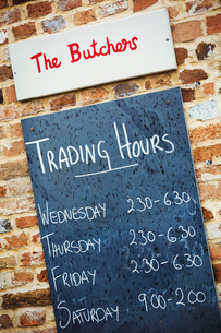 Blackboard with trading hours outside a butcher's shop.の写真素材 [FYI02858288]