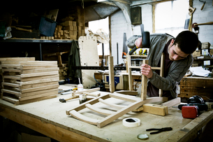 A man working in a furniture maker's workshop assembling a chair.の写真素材 [FYI02858291]