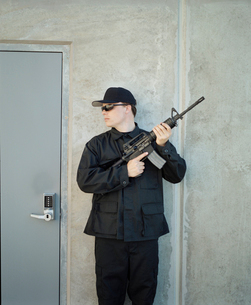 Man wearing special forces uniform and holding high powered semi-automatic rifle, guarding doorwayの写真素材 [FYI02858300]