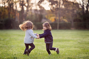 Two young girls, twin sisters, holding hands, playing on a lawn.の写真素材 [FYI02858303]