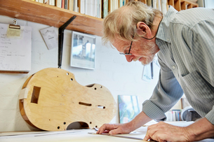 A violin maker at his drawing board drawing out the plans and outline for a new instrument.の写真素材 [FYI02858307]