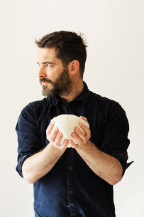 Baker holding a portion of bread dough shaped into a ball.の写真素材 [FYI02858308]