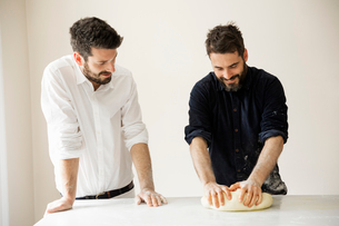 Two bakers standing at a table, kneading bread dough.の写真素材 [FYI02858311]