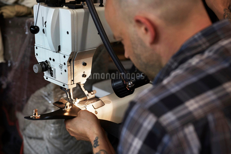 A man using an industrial sewing machine, stitching leather handmade goods.の写真素材 [FYI02858312]