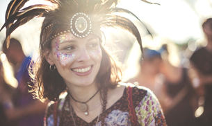 Young woman at a summer music festival wearing feather headdress and face painted, smiling.の写真素材 [FYI02858315]