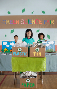 Three children standing behind presentations at the Green Science Fair.の写真素材 [FYI02858323]