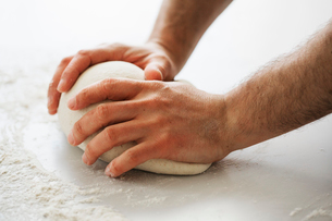 Close up of a baker kneading and shaping a portion of bread dough into a ball.の写真素材 [FYI02858327]