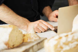Close up of a baker using a laptop computer, freshly baked bread.の写真素材 [FYI02858329]
