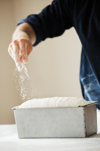 Close up of a baker sprinkling flour over bread dough in a metal baking tin.の写真素材 [FYI02858335]
