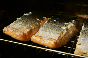 Close up of fish fillets on a rack in a fish smoker.の写真素材 [FYI02858340]