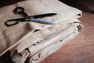 Upholstery workshop. Neutral coloured folded furnishing fabric and large scissors.の写真素材 [FYI02858344]