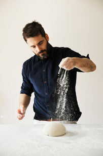 Baker standing at a table, liberally sprinkling flour over bread dough.の写真素材 [FYI02858349]