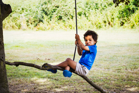 Portrait of young boy sitting on a tree swing.の写真素材 [FYI02858351]
